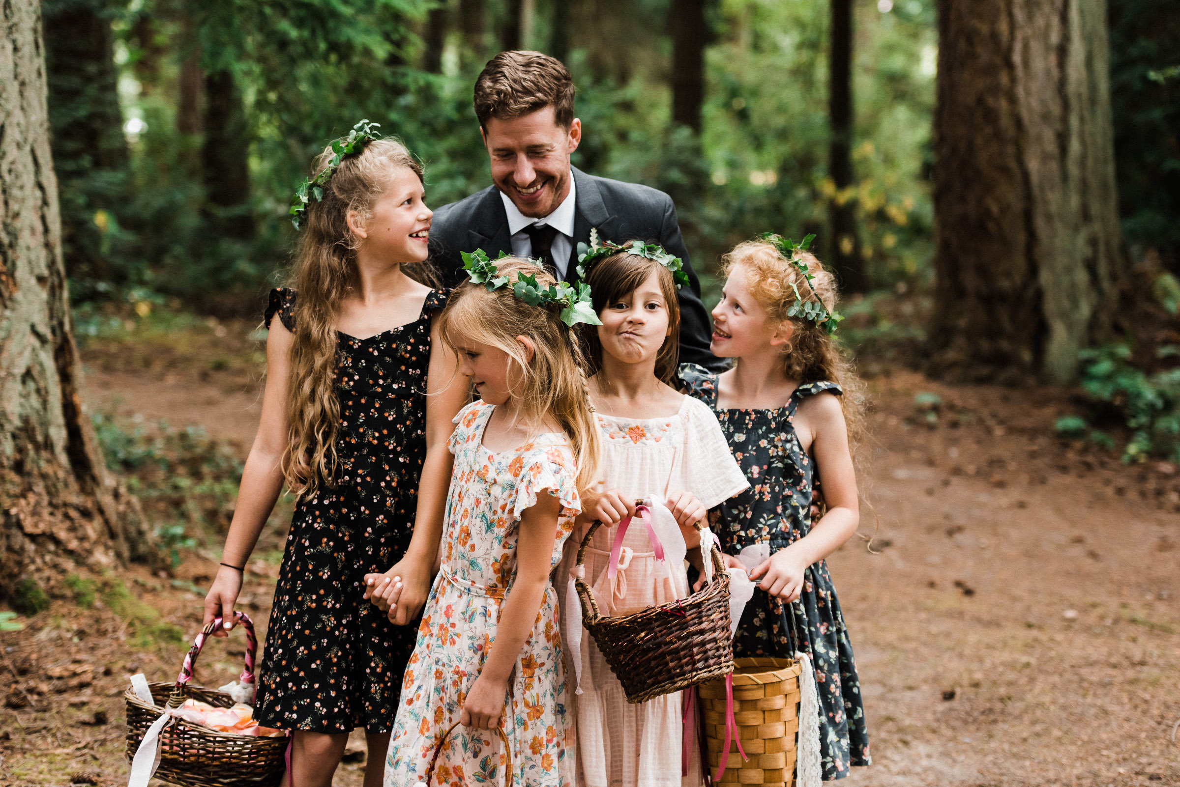 Groom and flower girls during a family friendly outdoor wedding with children in a Pacific Northwest old growth forest.