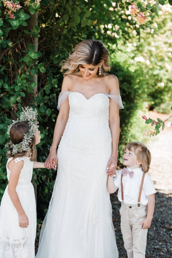 Bride laughing with the flower girl and ring bearer during a family first look at an outdoor wedding.