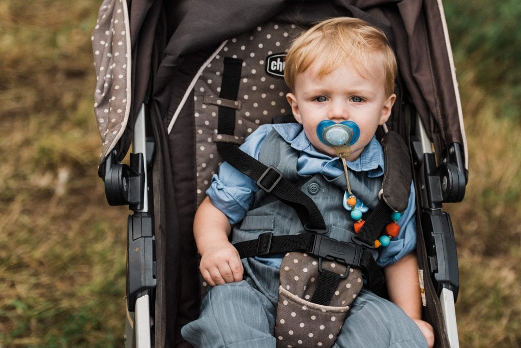 Child in a stroller at an outdoor elopement ceremony.