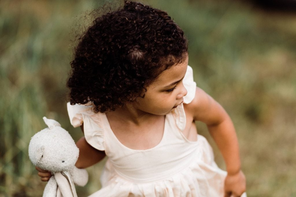 Little girl carrying her lovey at an outdoor elopement with kids.
