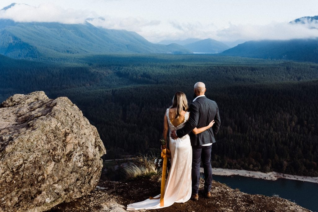 Wedding couple gazing at a mountain range during their adventurous elopement at Rattlesnake Ledge in North Bend, Washington.
