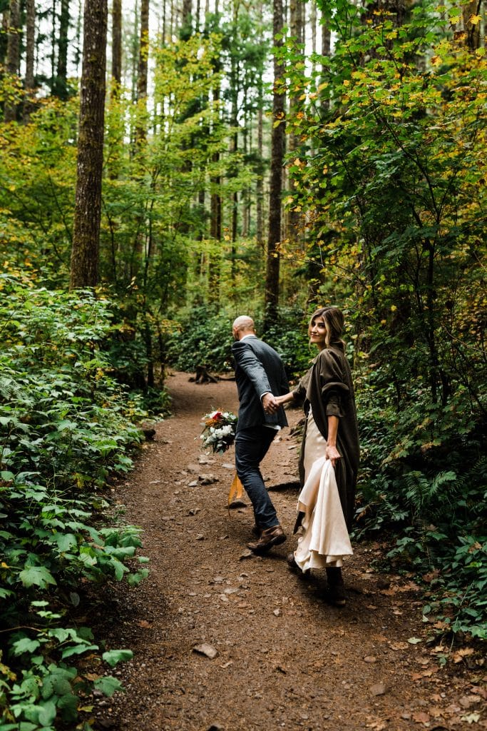Wedding couple holding hands on a hiking trail during their outdoor elopement in the Pacific Northwest.