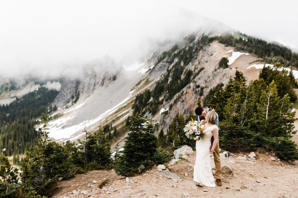 A couple kissing at a stunning overlook during their Mount Rainier National Park elopement.