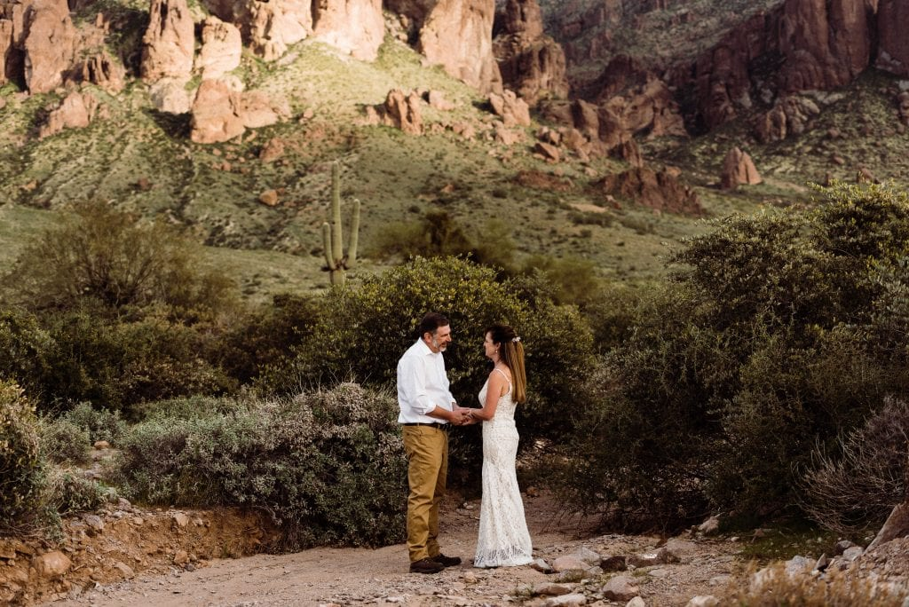 Couple saying their wedding vows during an elopement ceremony in the Superstition Mountain foothills of Lost Dutchman State Park, Arizona.