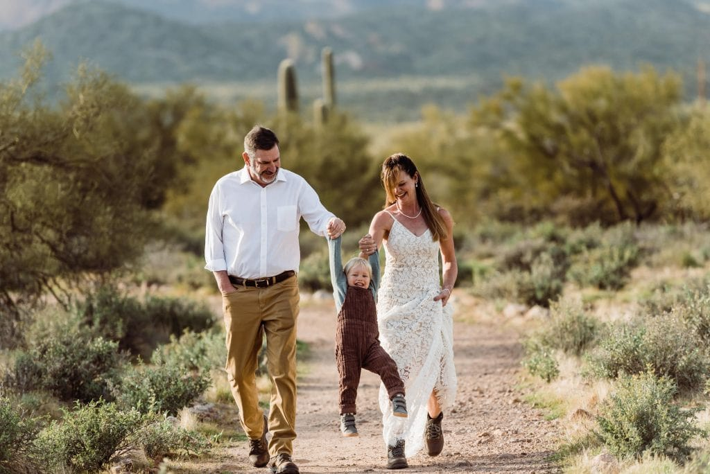 A bride and groom swing their child while walking through the desert at their Lost Dutchman State Park elopement.