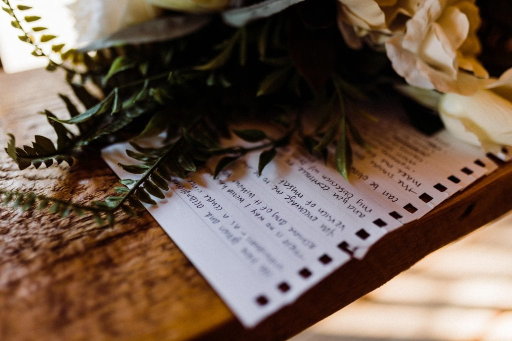 Handwritten vows sitting on a bench under a wedding bouquet.