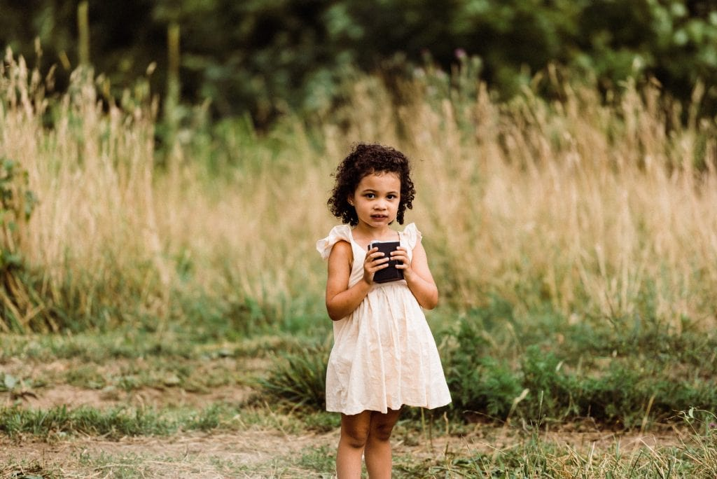 Little girl acting as the ring bearer during an outdoor elopement ceremony.