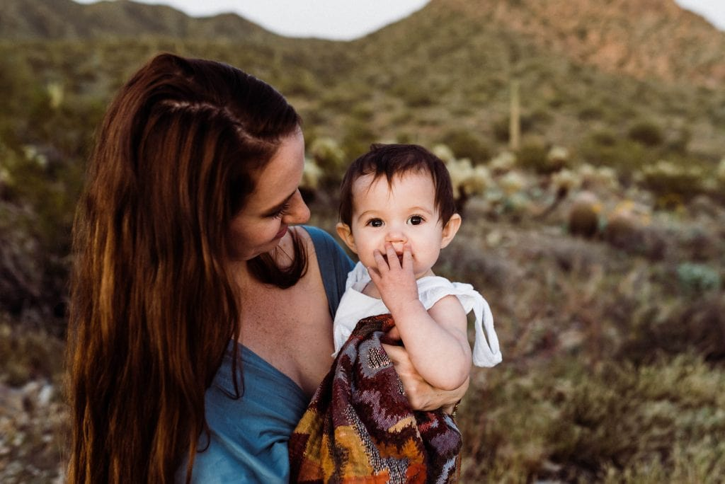 mom holding her baby in the Arizona desert during a hiking elopement with kids