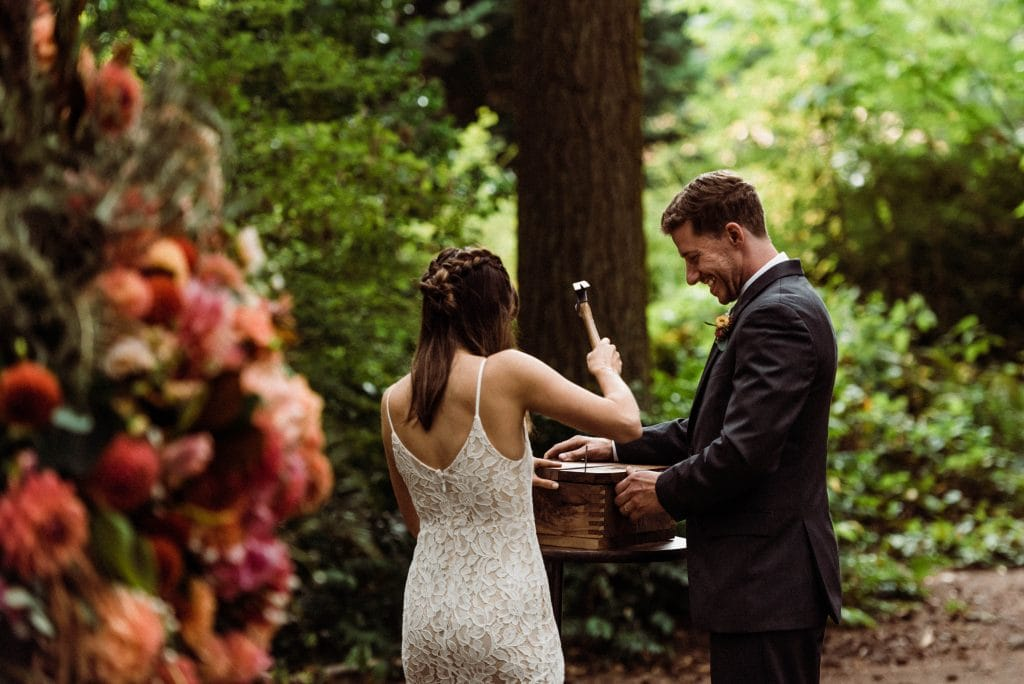 Bride and groom nailing a family time capsule during an outdoor elopement ceremony.