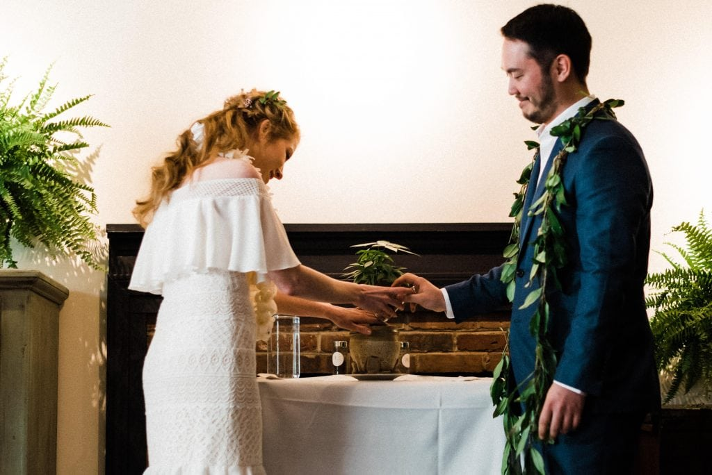 Couple adding soil to their tree during a tree planting unity ceremony at an intimate wedding.