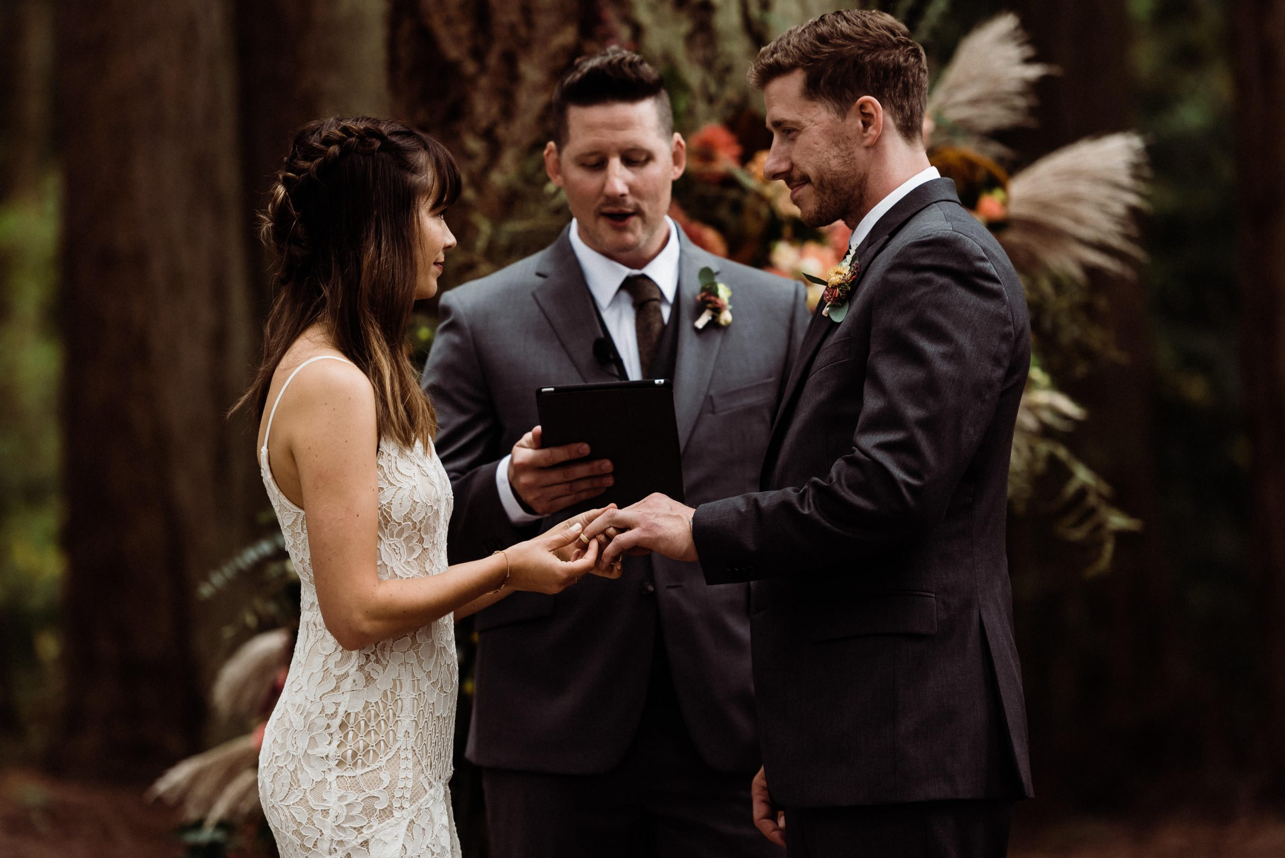 There are so many reasons to get married outdoor in the thick of nature like this couple exchanging rings during their forest wedding.