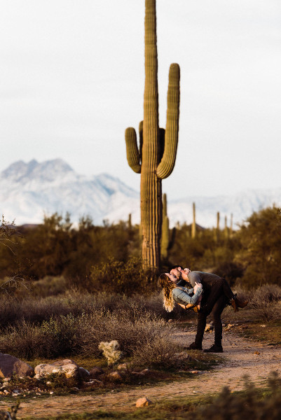 Couple kissing in Lost Dutchman State Park during adventurous session.