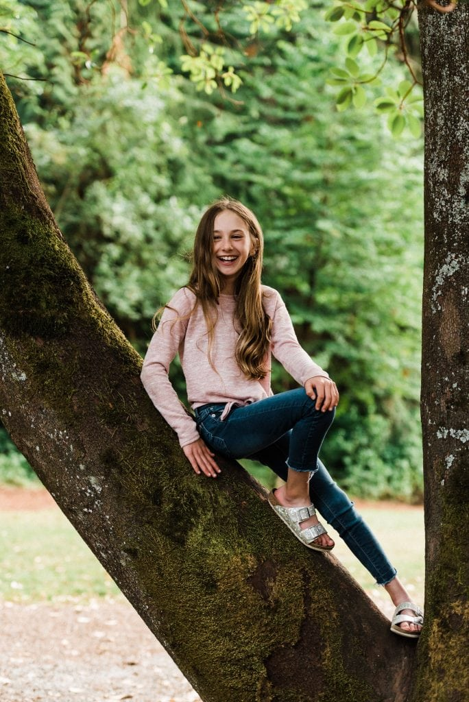 Child in a tree during a Seattle family photography session in Bellevue, Washington.