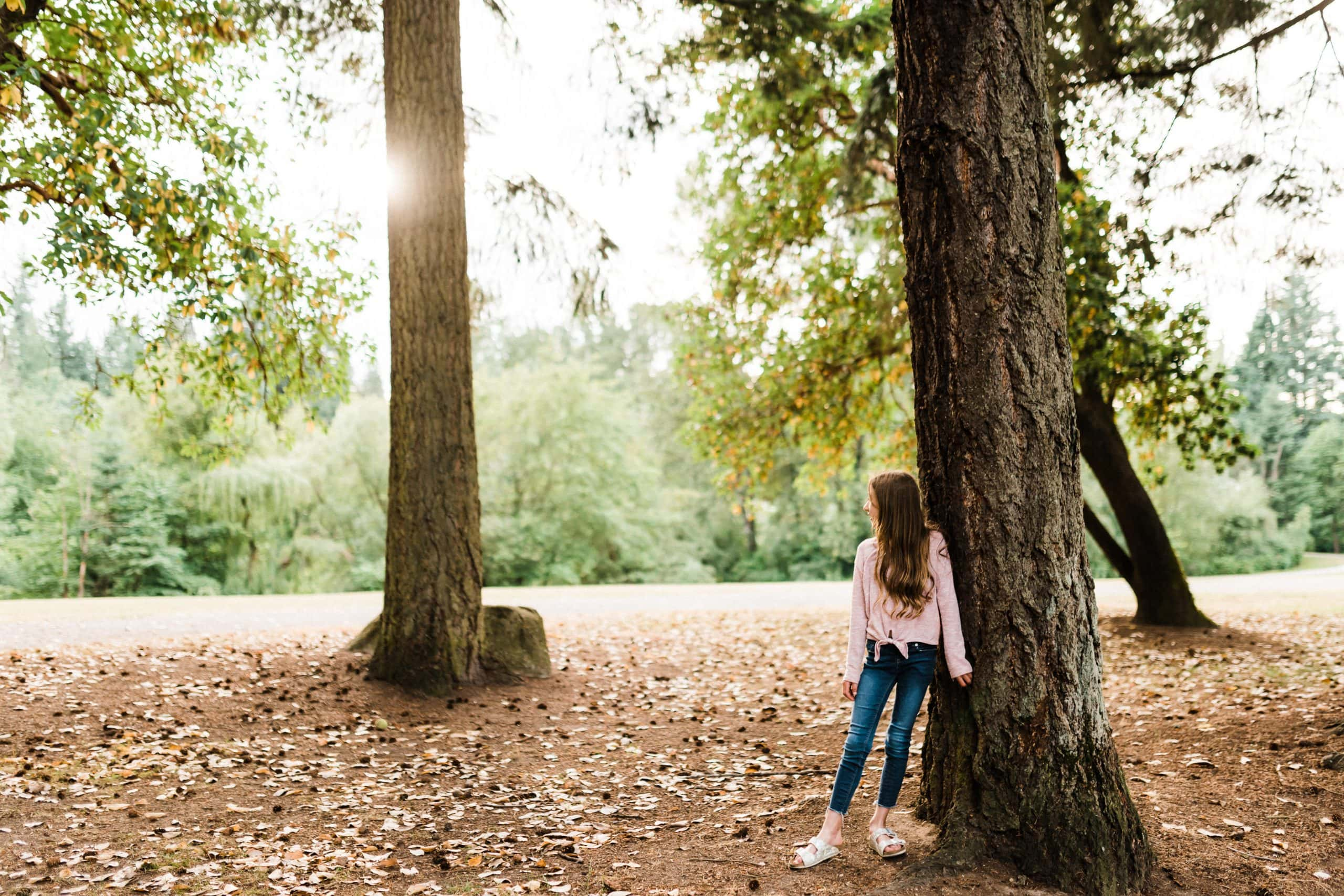 Child standing next to tree at a Bellevue, Washington park during a family session.
