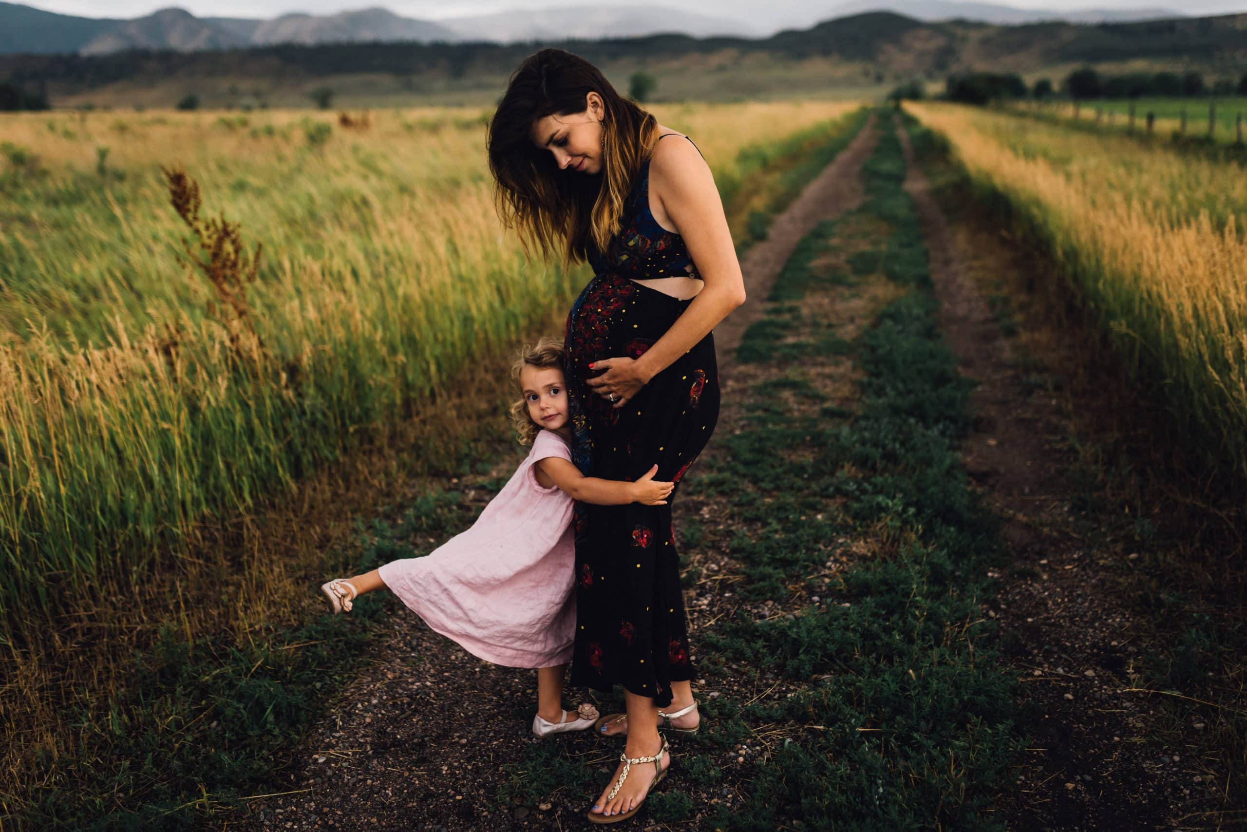 Girl embracing her pregnant mother in the foothills of the Colorado mountains.